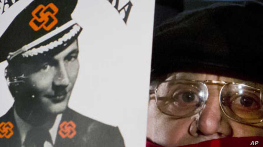 An anti-government protester holds a picture of the country's President Traian Basescu, altered to depict him as a Nazi, in Bucharest, Romania, Sunday, Jan. 22, 2012.