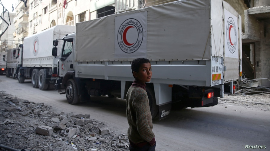 A boy stands as an aid convoy of Syrian Arab Red Crescent drives through the besieged town of Douma, Eastern Ghouta, Damascus.