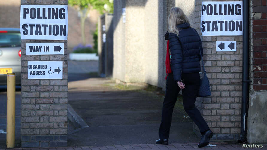 A woman enters a polling station as voting begins in local government elections in London, May 3, 2018.