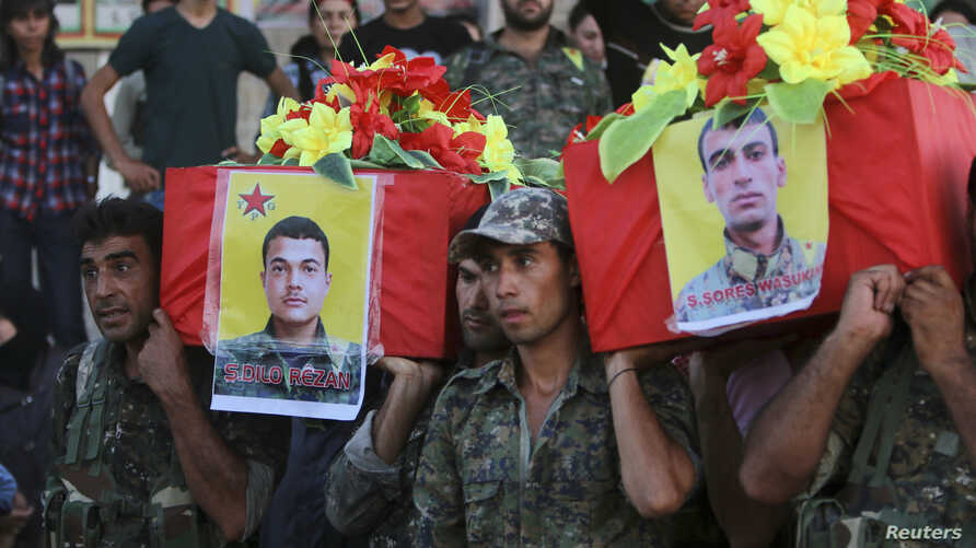 FILE - Members of the Kurdish People's Protection Units (YPG) carry coffins of their fellow fighters, who were killed during clashes with Islamic State fighters on the Iraqi-Syrian border, during their funeral in Ras al-Ain city, in Syria's Hasakah p...