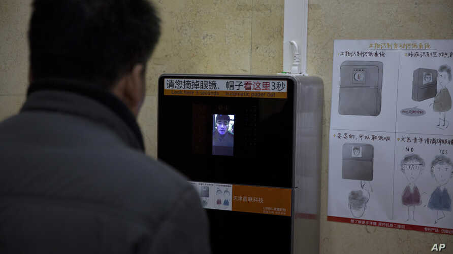FILE - A man tries out a facial recognition toilet paper dispenser at a toilet in the Temple of Heaven park in Beijing, China, March 21, 2017.