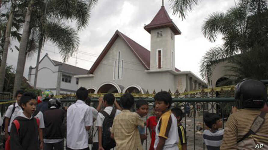 Indonesian youths gather outside the church that was attacked by Muslim hardliners in Temanggung, Central Java, Indonesia, February  8, 2011