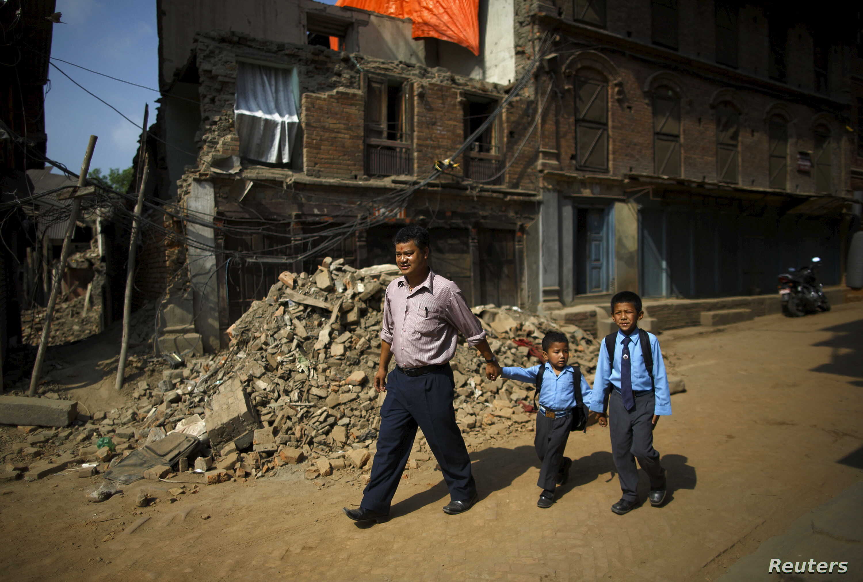 Birendra Karmacharya (L) walks past the debris of collapsed houses while holding the hand of his younger son Saksham Karmacharya, 4, along with his elder son Biyon Karmacharya (R), 9, as they head towards the school in Bhaktapur, Nepal, May 31, 2015....