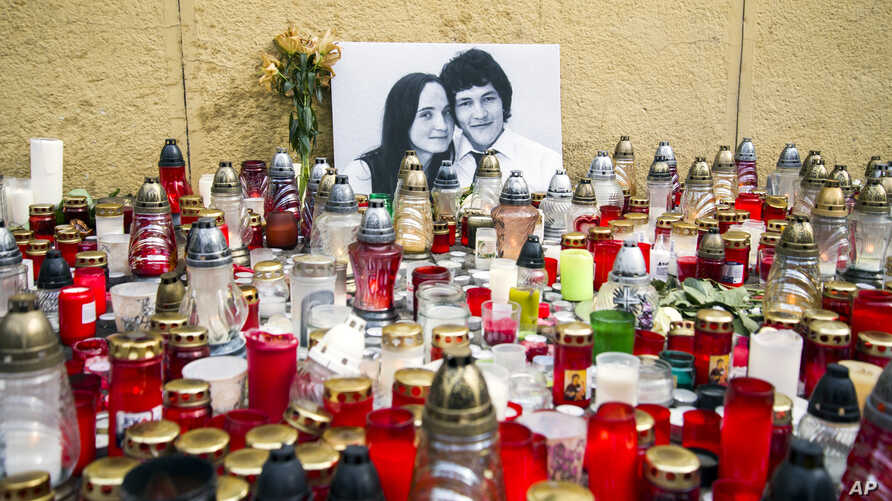 Candles are left in tribute to murdered Slovakian investigative reporter Jan Kuciak, 27, and his fiancee Martina, 27, at Slovak National Uprising Square in Bratislava, Feb. 27, 2018. A leading Slovak newspaper says organized crime may have been invol