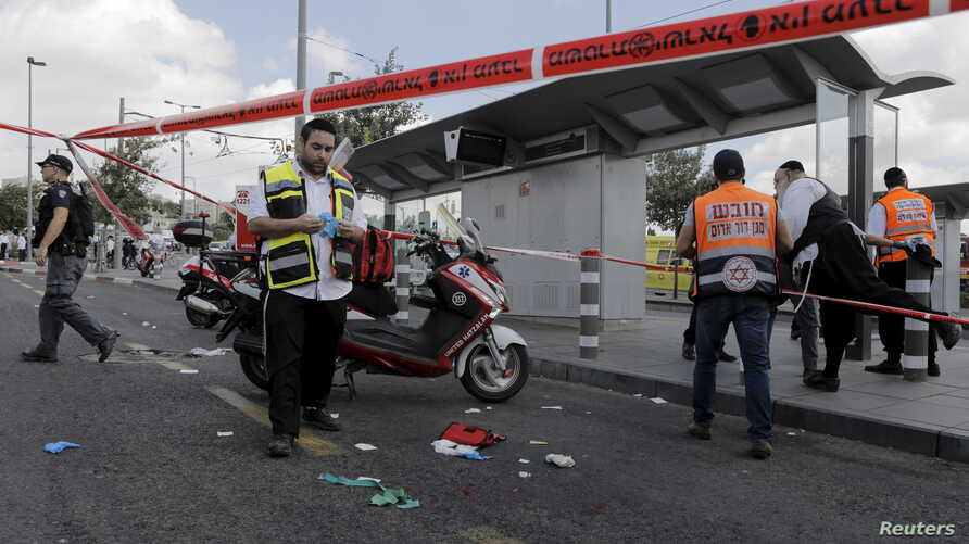Israeli emergency personnel stand at the scene of a stabbing in Jerusalem, Oct. 8, 2015. A Palestinian stabbed and wounded a Jewish seminary student on a main road in Jerusalem on Thursday and the assailant was arrested at the scene, police said.