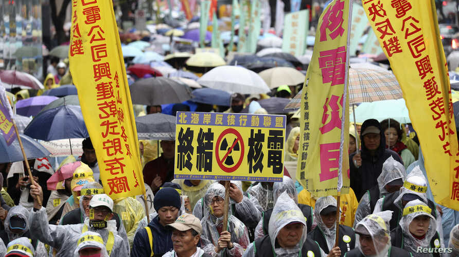 Demonstrators in raincoats and umbrellas march with banners and placards during an anti-nuclear protest on a street, amid rainfall in Taipei, March 8, 2014.