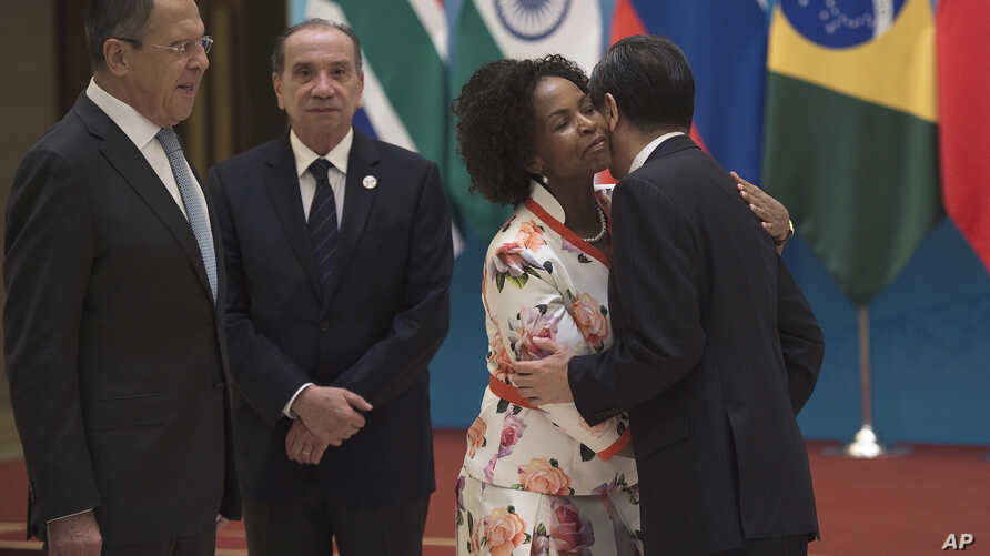 South Africa's Foreign Minister Maite Nkoana-Mashabane, second from right, hugs China's Foreign Minister Wang Yi as Russia's Foreign Minister Sergey Lavrov, left, and Brazil's Foreign Minister Aloysio Nunes stand before the opening of the BRICS forei