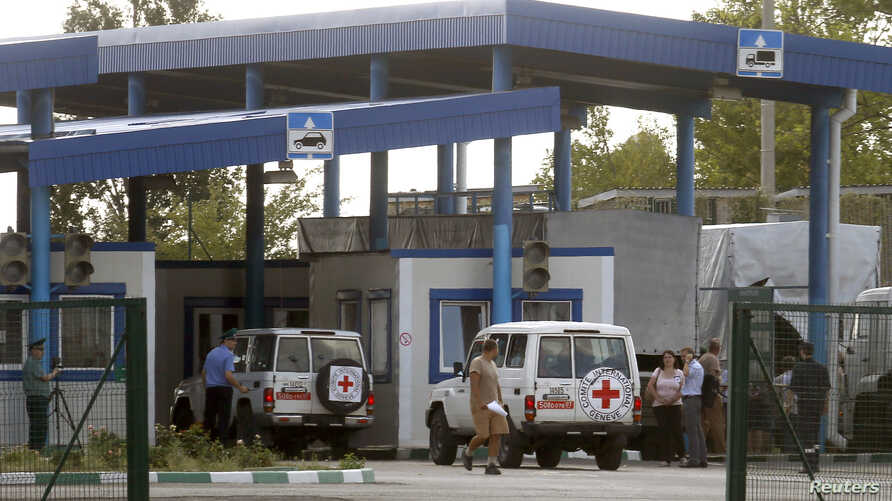 "Cars of the Red Cross and trucks of a Russian convoy carrying humanitarian aid for Ukraine are seen at a Russia-Ukraine border crossing point ""Donetsk"" during a control check in Rostov Region, Aug. 21, 2014."