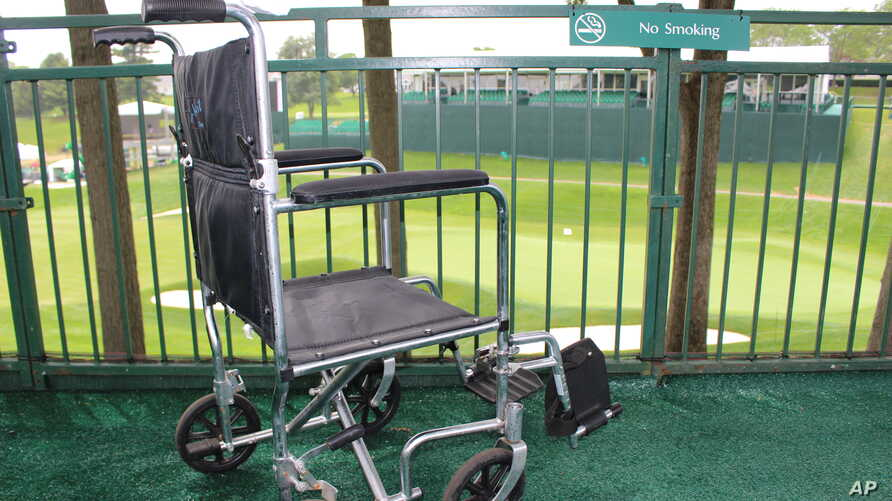 FILE - A wheelchair sits in the viewing area of the ALS Center of Excellence at the TPC River Highlands golf course, June 19, 2017. Tournament officials built a special tent and viewing area for fans with amyotrophic lateral sclerosis.