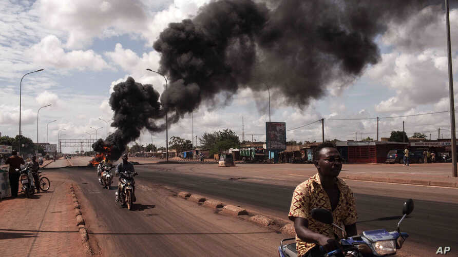 Tires burn in the background  as people protest against the recent coup in  Ouagadougou, Burkina Faso, Sept. 19, 2015.