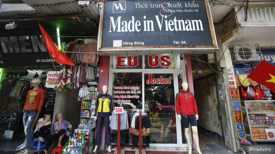 FILE - Vendors sit outside a shop selling clothes in Hanoi October 3, 2014.