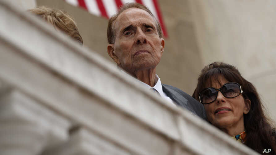 FILE - Former Sen. Bob Dole watches as President Donald Trump speaks during a Memorial Day ceremony at Arlington National Cemetery, May 29, 2017, in Arlington, Virginia.