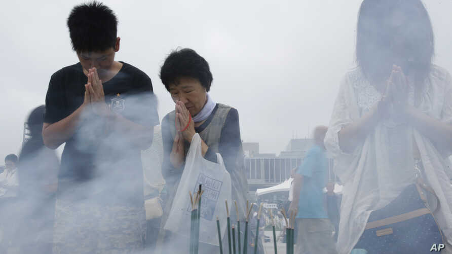 People pray for the atomic bomb victims at the Hiroshima Peace Memorial Park in Hiroshima, western Japan, Aug. 6, 2013.