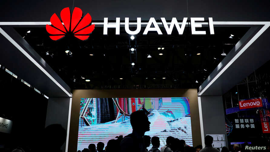 FILE - People walk past a sign board of Huawei at CES (Consumer Electronics Show) Asia 2018 in Shanghai, China, June 14, 2018.
