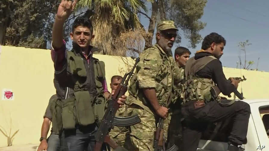 In this image made from video posted online by Qasioun News Agency, members of a Turkish-backed Syrian opposition force patrol in Dabiq, Syria, Oct. 16, 2016.