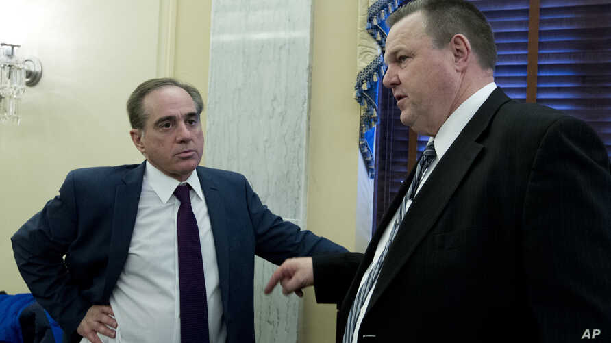 FILE - Veterans Affairs Secretary David Shulkin speaks with Sen. Jon Tester, D-Mont. (R), after testifying before the Senate Committee on Veterans Affairs on Capitol Hill, March 21, 2018, in Washington.