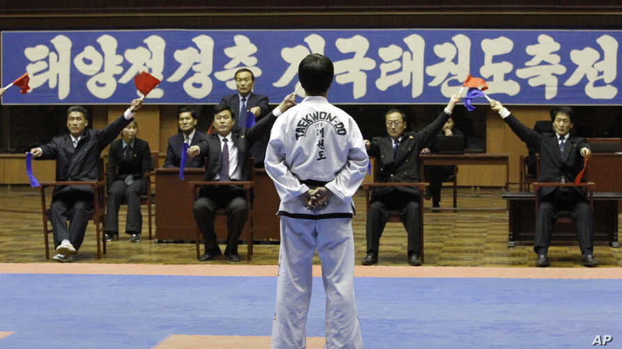 """FILE - A North Korean participant in a national Taekwondo festival is judged in front of a sign in Korean that reads """"National Taekwondo Festival for Celebrating Day of the Sun"""" at the Taekwondo Hall in Pyongyang, North Korea, April 7, 2012."""