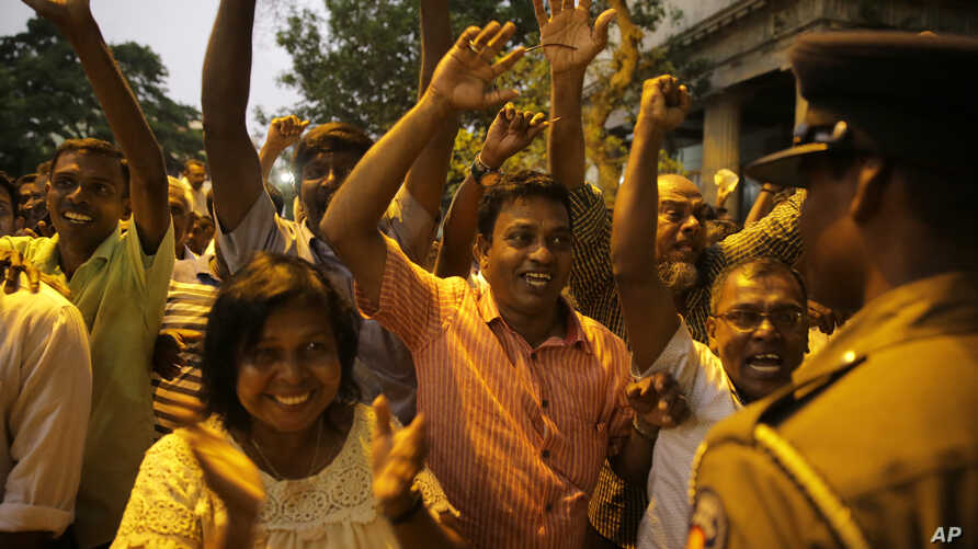 Supporters of Sri Lanka's ousted PM Ranil Wickremesinghe shout slogans as they celebrate after the Supreme Court suspended dissolution of parliament by President Sirisena, outside the court complex in Colombo, Sri Lanka, Nov. 13, 2018.