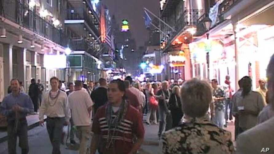 Tourists and locals walk down Bourbon Street in New Orleans