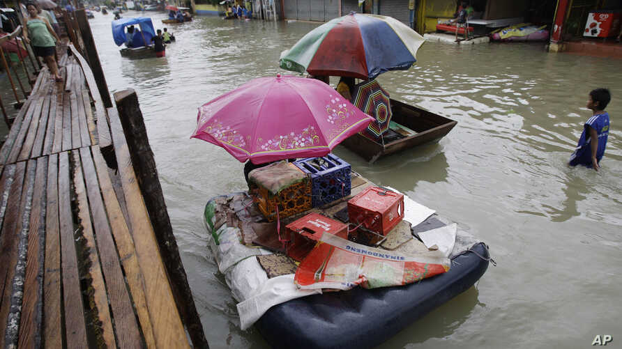 Residents use makeshift floats as others cross a makeshift bridge built over a flooded road in suburban Pasig, east of Manila, Philippines, August 15, 2012.
