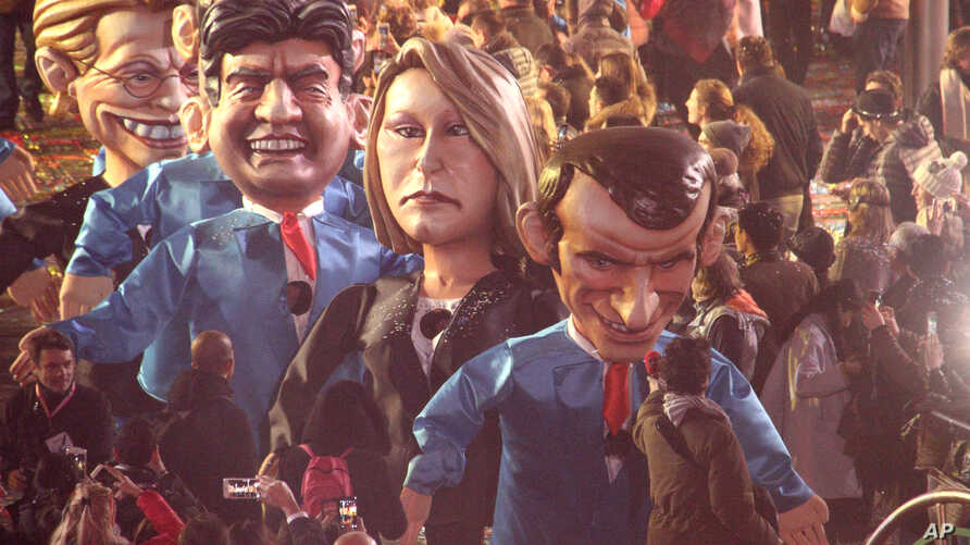Big heads showing left to right, French presidential election candidate for Leftist Front Jean-Luc Melanchon, far right regional leader for southeastern France, Marion Marechal-Le Pen and Presidential candidate Emmanuel Macron, parade during 133th Ni