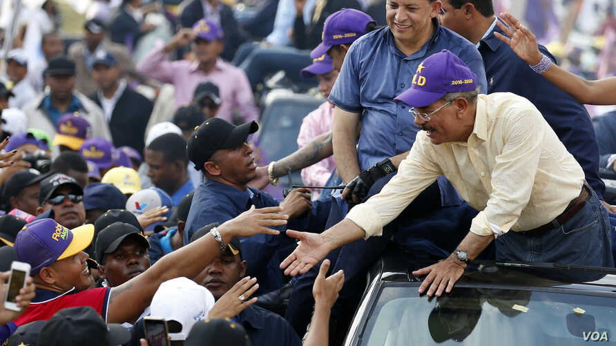 Dominican Republic President and Dominican Liberation Party (PLD) presidential candidate Danilo Medina (R) greets his supporters during a march in Santo Domingo, Dominican Republic, May 12, 2016.