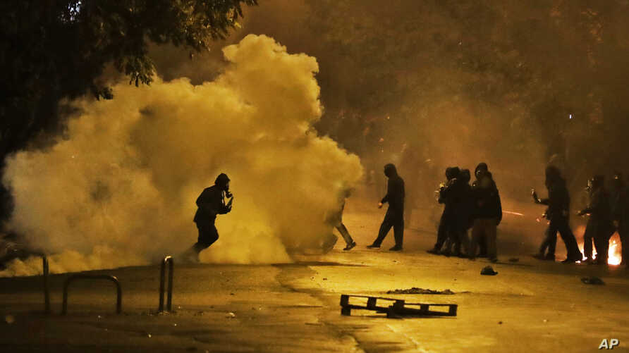 Protesters try to avoid the effects of tear gas fired by riot police during clashes in Athens, Nov. 17, 2017.