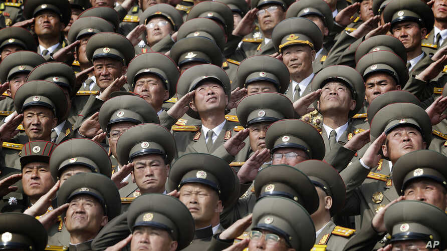 In this, April 15, 2017, photo, North Korean soldiers salute as their national anthem is played during a military parade to celebrate the 105th birth anniversary of Kim Il Sung, in Pyongyang.