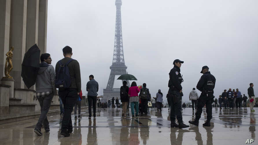 People walk past by French police officers, as they patrol at Trocadero plaza with the Eiffel Tower in the background in Paris, France, Saturday, May 6, 2017. Voting for France's next president starts in overseas territories and French embassies abro