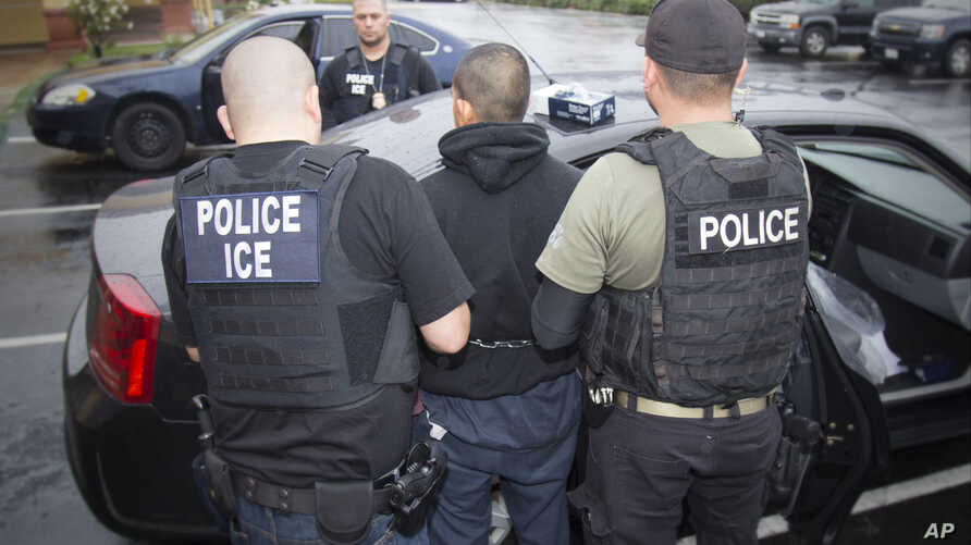 FILE - photo released by U.S. Immigration and Customs Enforcement shows foreign nationals being arrested this week during a targeted enforcement operation conducted by U.S. Immigration and Customs Enforcement (ICE).