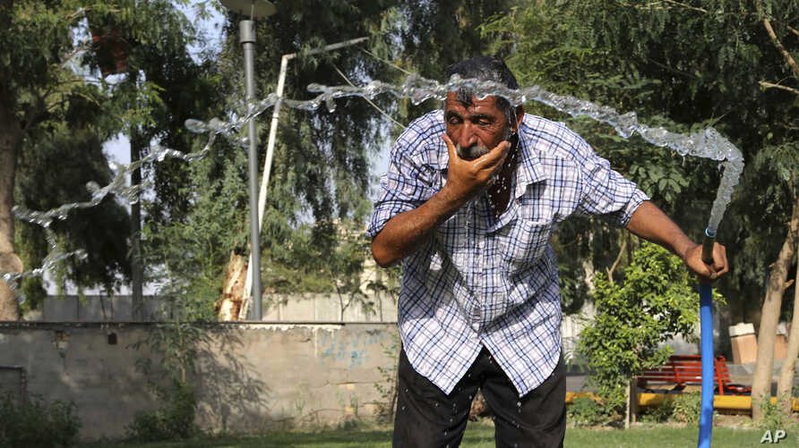 An Iraqi man cools himself with water in central Baghdad, Iraq, July 16, 2015.