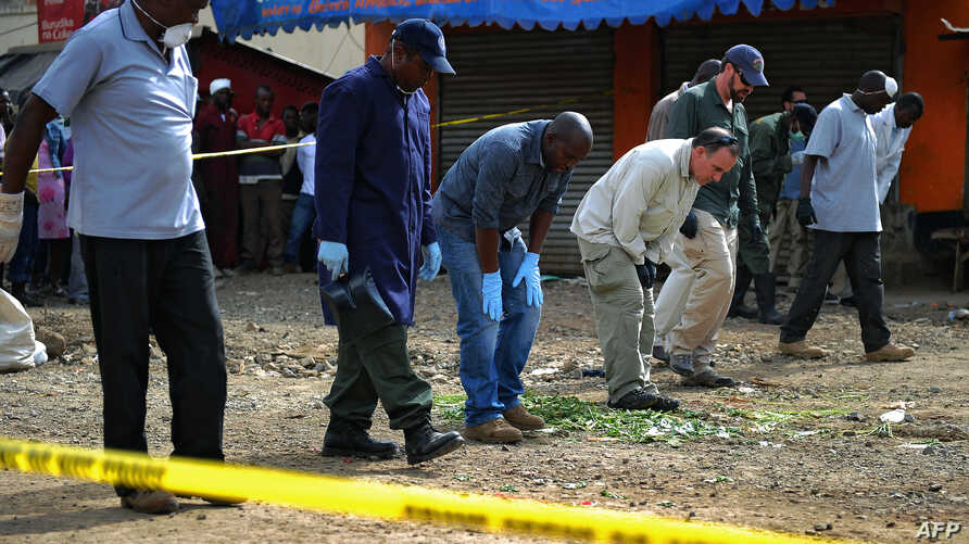 Forensic teams search for evidence at the scene of a bomb blast in the Somali district of Eastleigh, in Nairobi, April 1, 2014.