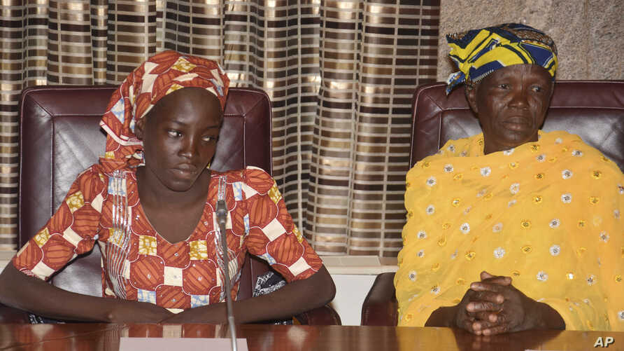 FILE - Amina Ali, left, the first rescued Chibok schoolgirl, and her mother, Binta Ali Nkeki attend a meeting with Nigeria's President Muhammadu Buhari at the Presidential palace in Abuja, Nigeria.