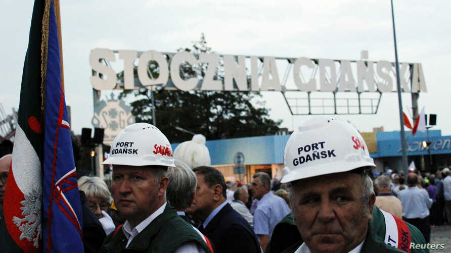 Workers wearing Solidarity safety helmets are seen in front of the shipyard entrance during the 37th anniversary of emerging Solidarity trade union at the historic shipyard area in Gdansk, Poland, Aug. 31, 2017.