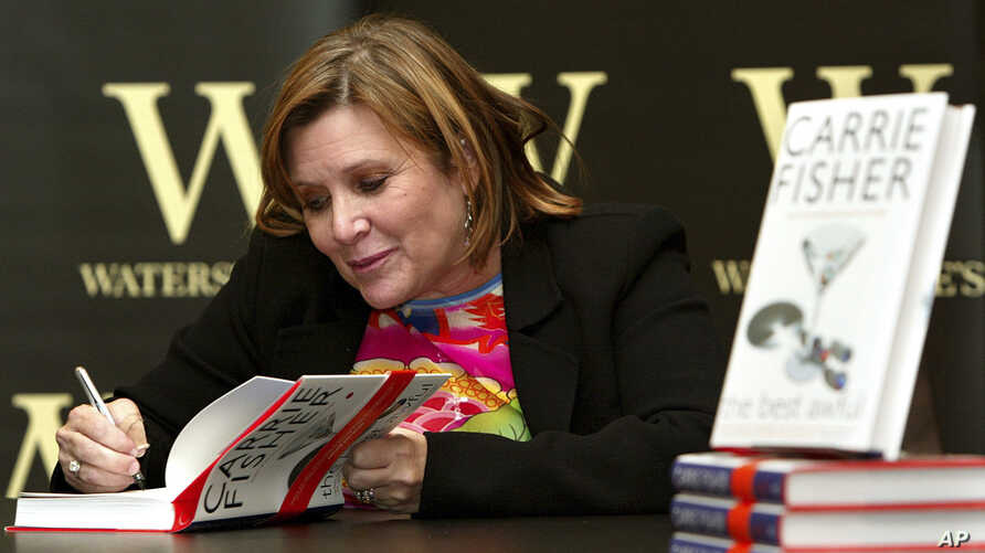 "FILE - In this Feb. 20, 2004, photo, ""Star Wars"" actress, humorist and author Carrie Fisher autographs her book ""The Best Awful"" at a promotional event in London."