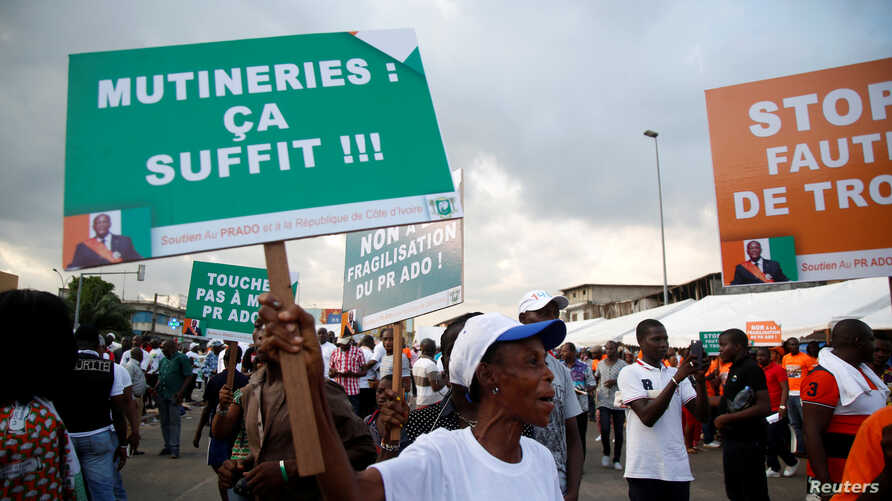 """A partisan of the ruling party RDR (Rally of the republicans) holds a placard during a rally against the mutiny close to the military headquarters in Abidjan, Ivory Coast, May 13, 2017. The placard reads, """"Mutinies: it's enough""""."""
