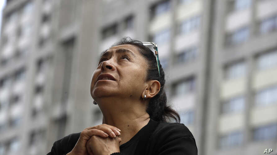A woman prays during an outdoor Mass service, held outside Saint James Apostle Parish, because the church building suffered some damage during the 7.1-magnitude earthquake, in the Plaza de las Tres Culturas in Tlatelolco, Mexico City, Sept. 24, 2017.