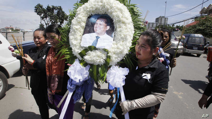 Cambodian community activists carry a wreath during the funeral procession of government critic Kem Ley, pictured, in Phnom Penh, Cambodia, July 11, 2016.