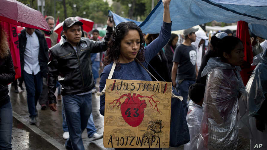 """FILE - A demonstrator with a banner that in Spanish reads """"Justice 43 Ayotzinapa"""" in reference to the 43 missing students from a rural teachers college marches in protest, marking 30 months since their disappearance, in Mexico City."""