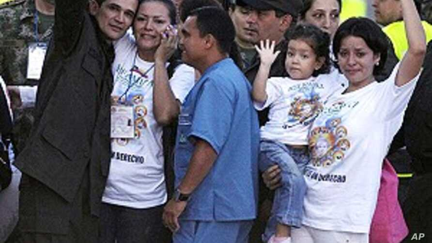 Carlos Jose Duarte, a Colombian policeman recently freed by FARC rebels, waves at the media with his relatives as he arrives at Villavicencio's airport April 2, 2012.