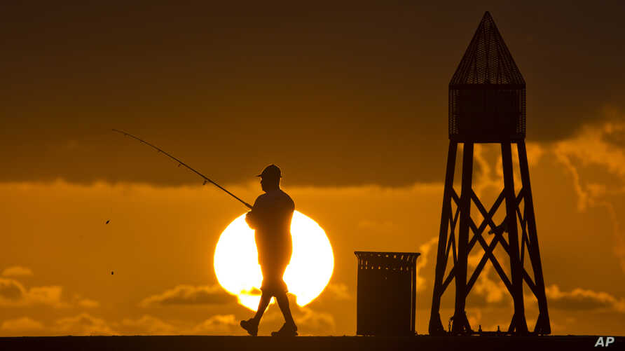 FILE - A fisherman prepares to cast a line as the sun rises behind him as he fishes off a jetty into the Atlantic Ocean, in Bal Harbour, Florida, July 14, 2016.
