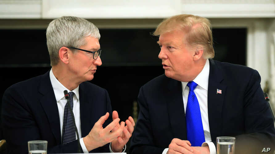 President Donald Trump talks to Apple Inc. CEO Tim Cook during the American Workforce Policy Advisory Board's first meeting in the State Dining Room of the White House in Washington, Wednesday, March 6, 2019.