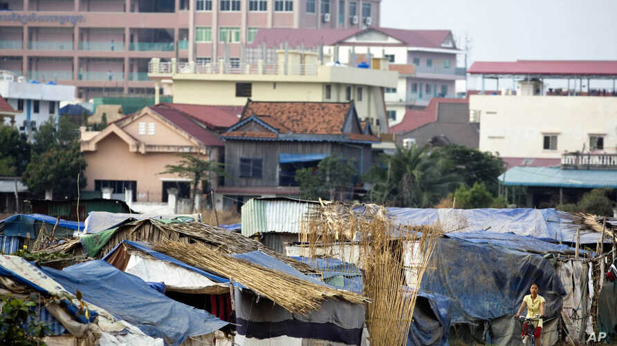A young Cambodian woman rides a bicycle near slum homes, Feb. 19, 2009, on the outskirts of Phnom Penh, Cambodia.