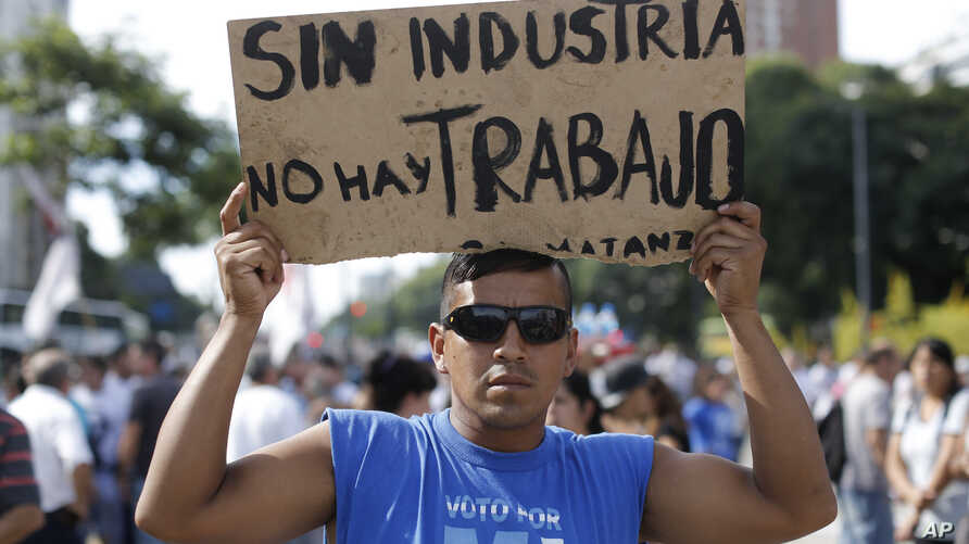 "A demonstrator holds a sign that reads in Spanish ""Without industry there is no work"" during a labor march in Buenos Aires, Tuesday, March 7, 2017."