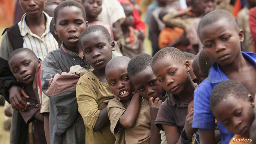 Refugee children, displaced by continued fighting in north Kivu province in the Democratic Republic of Congo (DRC), wait for food in the Nyakabande refugee transit camp in Kisoro town, 521 km (324 miles) southwest of Uganda's capital Kampala, July 13