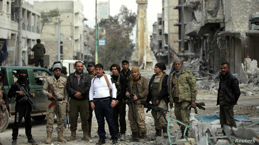 Rebel fighters pose for a picture in a damaged neighborhood in the northern Syrian town of al-Bab, Syria, March 4, 2017.