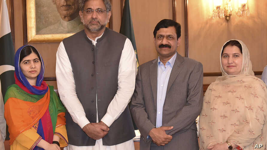 In this photo released by the Press Information Department, Pakistani Nobel Peace Prize winner Malala Yousafzai, left, and her parents pose for a photograph with Shahid Khaqan Abbasi, second from left, Prime Minister of Pakistan in Islamabad, Pakista