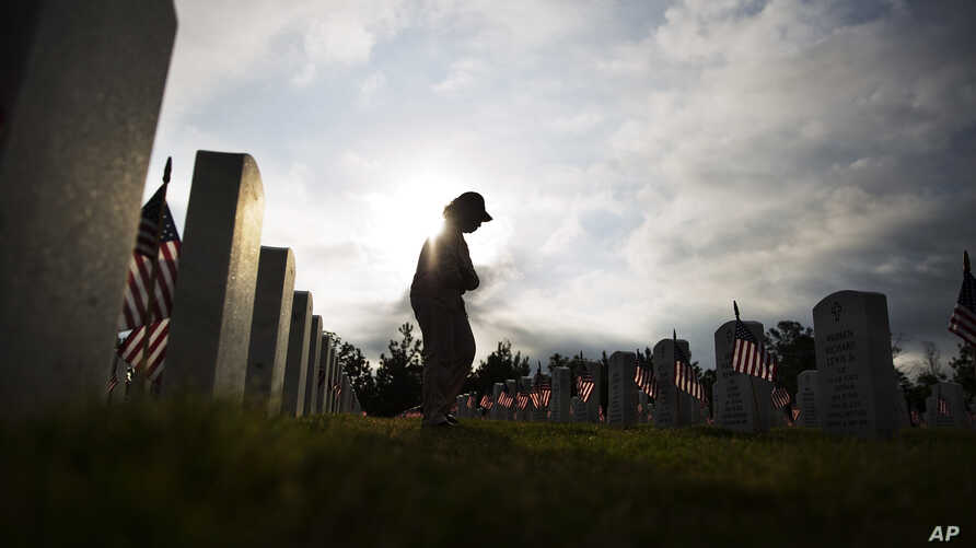Lucille Williams walks through Georgia National Cemetery while visiting the grave of her late husband, Korean War veteran Sgt. 1st Class Alvin Williams, in honor of Memorial Day, Monday, May 25, 2015, in Canton, Ga. (AP Photo/David Goldman)