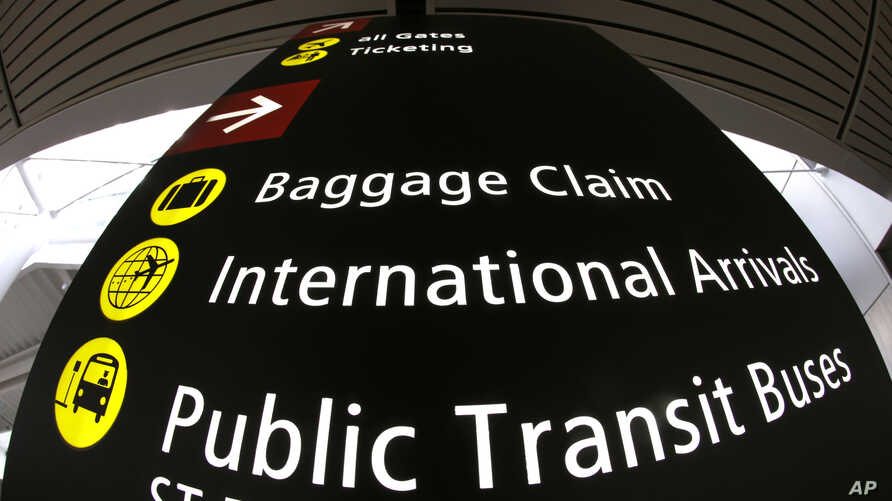 A sign for International Arrivals is shown at the Seattle-Tacoma International Airport, June 26, 2017, in Seattle. The Supreme Court said Monday that President Donald Trump's travel ban on visitors from Iran, Libya, Somalia, Sudan, Syria and Yemen ca