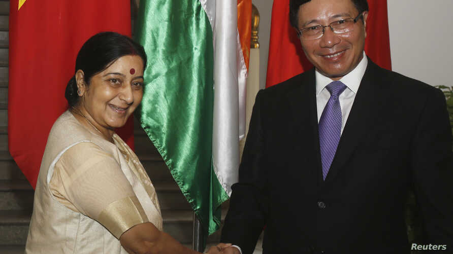 India's Foreign External Affairs Minister Sushma Swaraj (L) poses for a photo with Vietnam's Deputy Prime Minister and Foreign Minister Pham Binh Minh before their meeting in Hanoi, August 25, 2014.